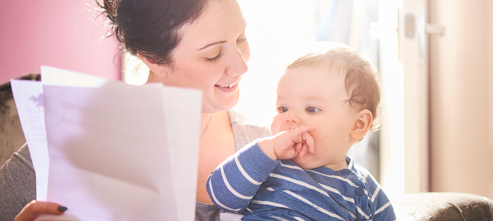 A woman smiling with at her baby while holding paers